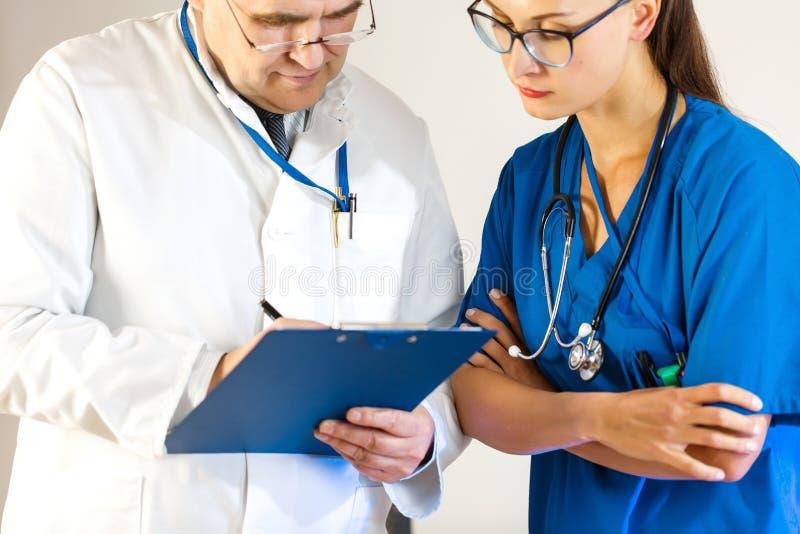 Старший доктор пишет данные в карте пациента, другой доктор смотрит стоковые изображения rf