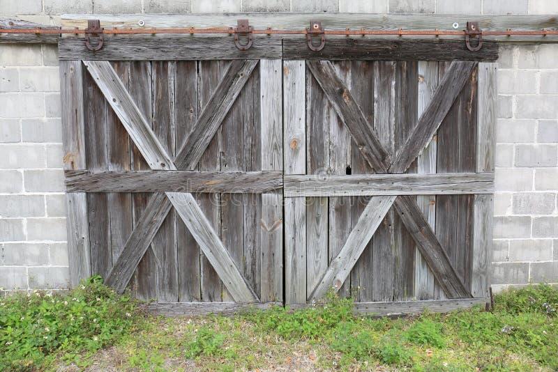 Старые выдержанные серые деревянные двери амбара с ржавым оборудованием стоковая фотография rf