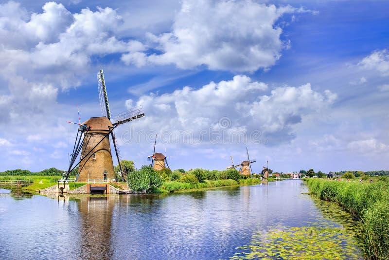 Старые мельницы ветра около голубого канала на летний день на известном Kinderdijk, Голландии стоковая фотография