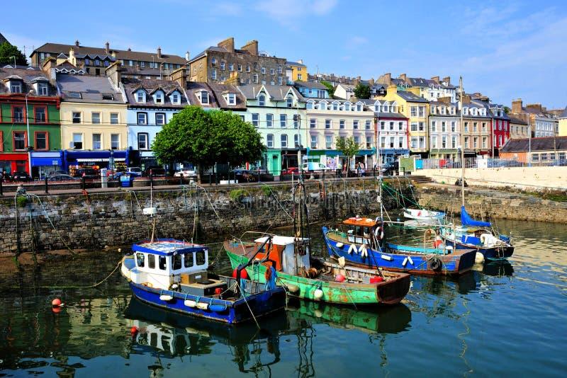 Старые шлюпки и красочные здания гавани, Cobh, пробочка графства, Ирландия стоковые изображения