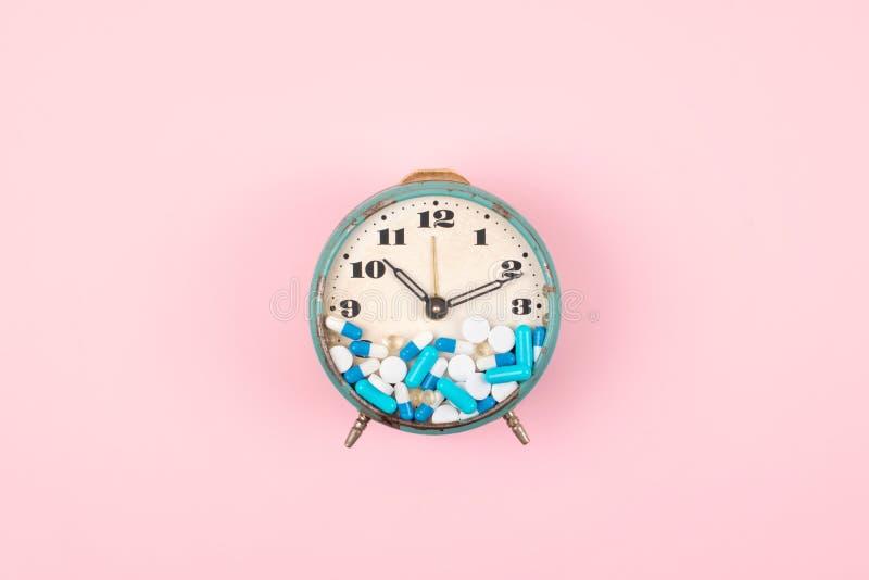 Старый будильник с планшетами, медициной и таблетками на циферблате на розовой предпосылке красочные капсулы на часах Здравоохран стоковая фотография rf