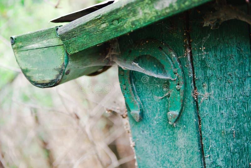 Старый ботинок лошади пригвозженный на деревянной стене старого зеленого дома - удачливого будущего стоковая фотография rf