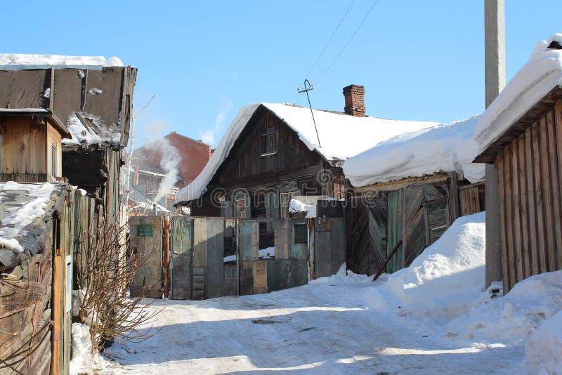 Старый деревянный дом в деревне с флигелями в зиме стоковое изображение