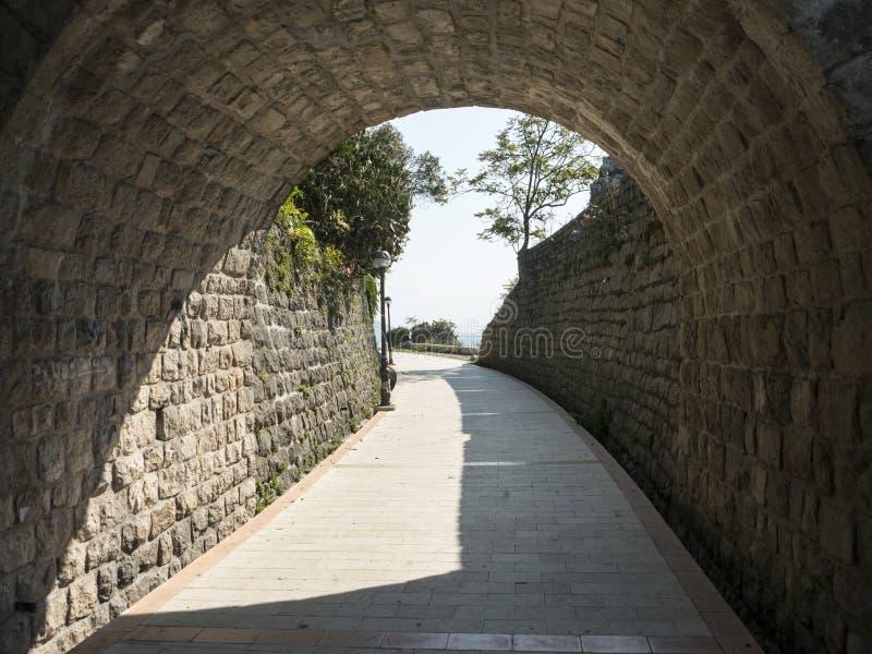 Старый длинный каменный тоннель кирпича с взглядом пляжа лета на ем другая сторона стоковое изображение