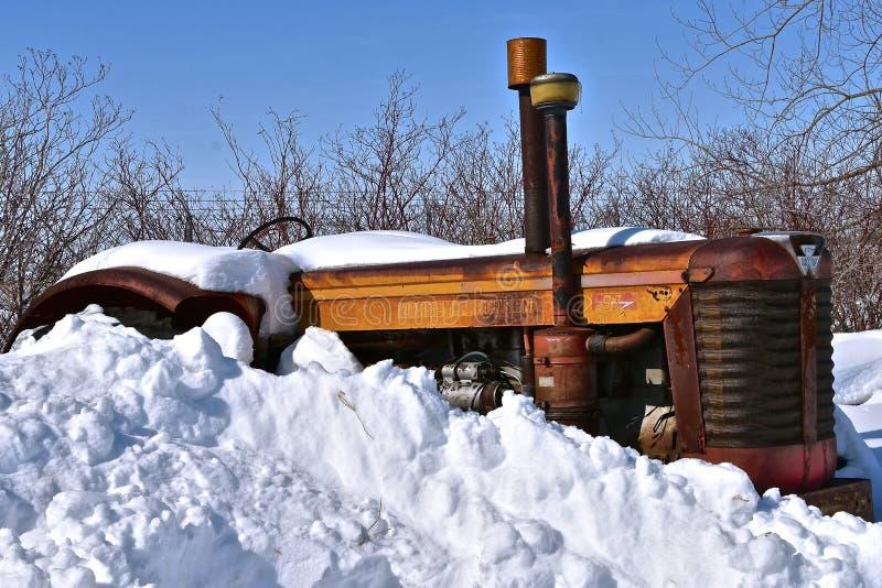 Старый трактор Massey Ferguson 97 трактора частично похороненный в глубоком снеге стоковое изображение