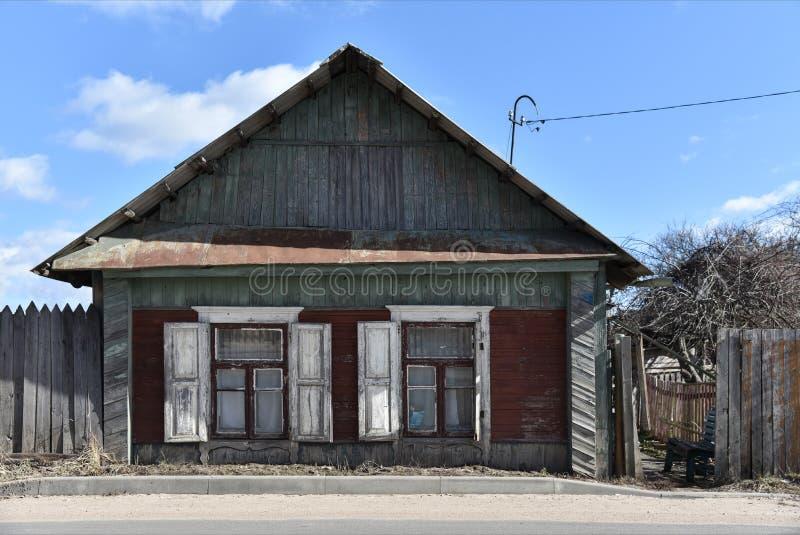 Старый рушась деревянный дом около дороги в России стоковые фотографии rf