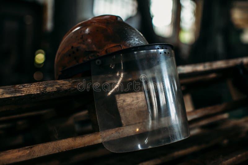 Старый оранжевый шлем конструкции на фабрике, положил дальше ручку стоковые фото