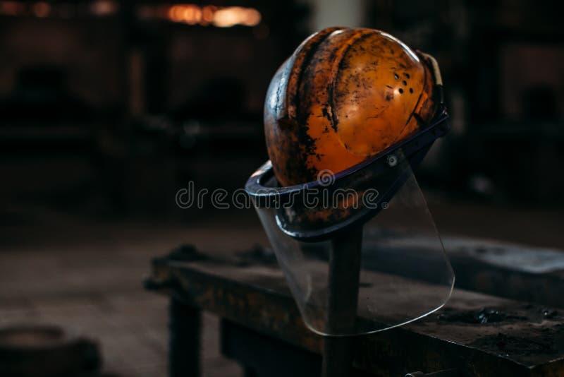 Старый оранжевый шлем конструкции на фабрике, положил дальше ручку стоковые изображения