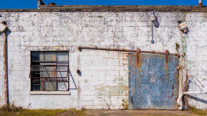 Старое здание текстурировало поверхность с ржавыми стальными дверью и окном стоковые фото