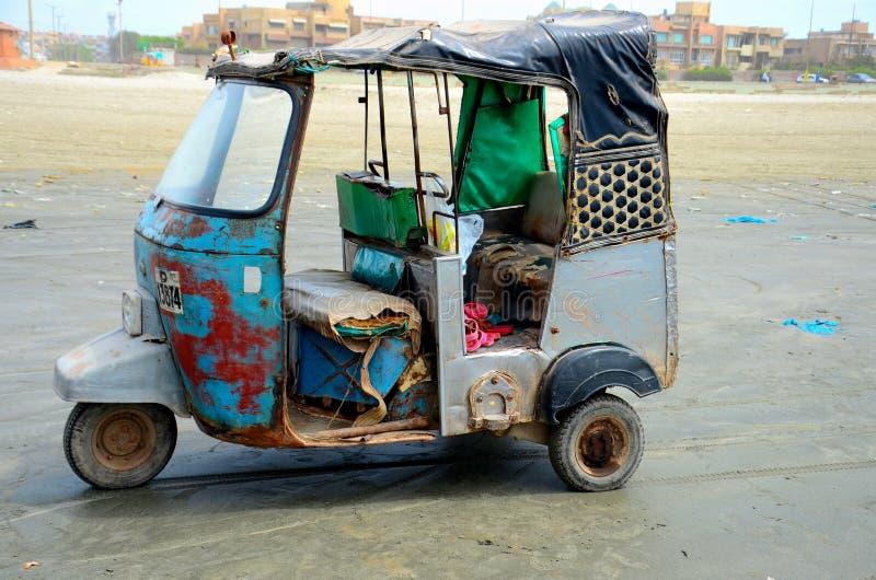 Старое разрушанное tuk tuk рикши на пляже Клифтон Карачи Пакистане вида на море стоковое фото rf