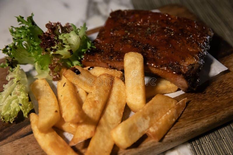 Стейк сулоя свинины гриля с французским картофелем фри на деревянном блюде прямоугольника стоковые фотографии rf