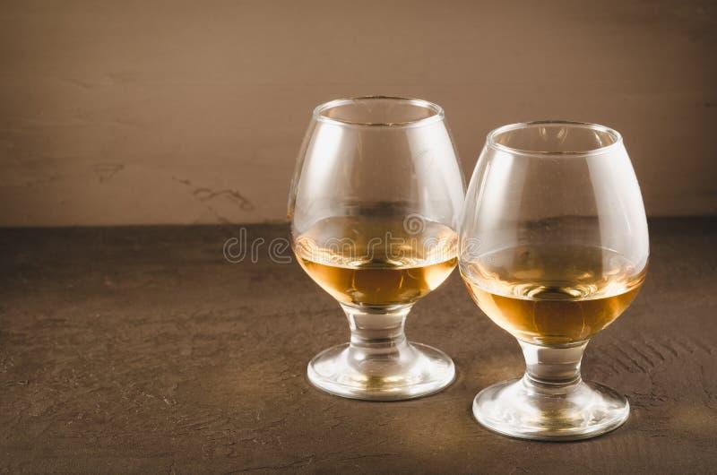 2 стекла с коньяком/2 стеклами с коньяком на темной каменной предпосылке, выборочным фокусом стоковая фотография