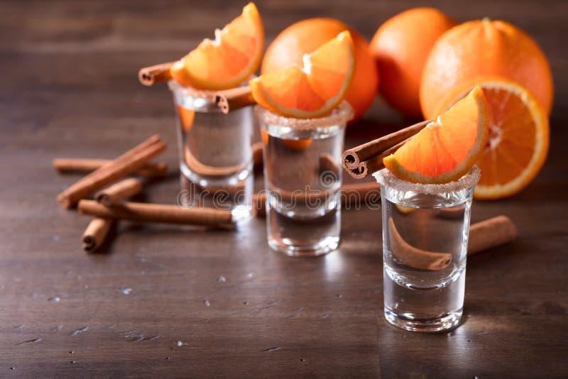 Стекла текила с оранжевыми кусками и ручками циннамона стоковое фото