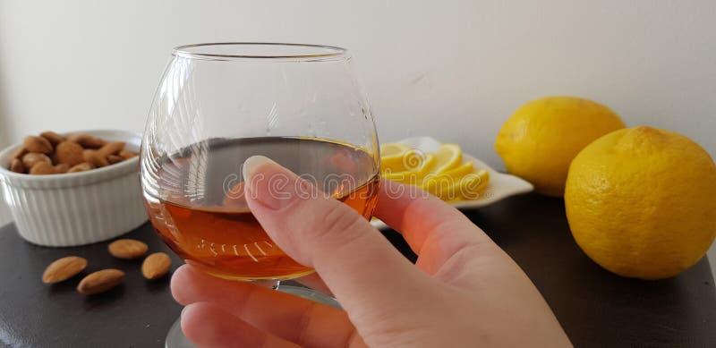 стеклянная половина полная с рябиновкой над коричневой таблицей с миндалинами и лимонами стоковое фото