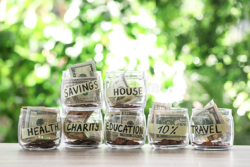 Стеклянные опарникы с деньгами для различных потребностей на таблице стоковое фото rf