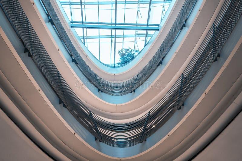 Стеклянный потолок и спиральные перила в современном здании стоковое изображение