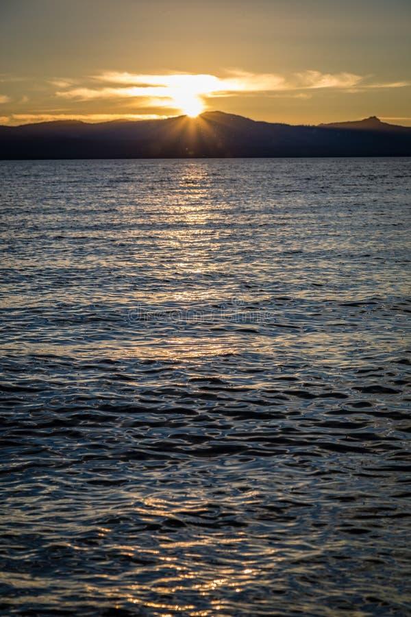 Стекловидная вода с золотой установкой солнца за плоскими горами в расстоянии смотря от пляжа берега озера на Лаке Таюое стоковая фотография