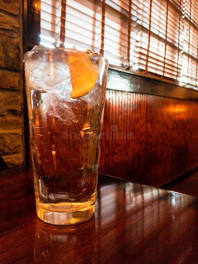 Стекло воды со льдом с лимоном на деревянном столе в установке ресторана Отсутствие людей стоковая фотография
