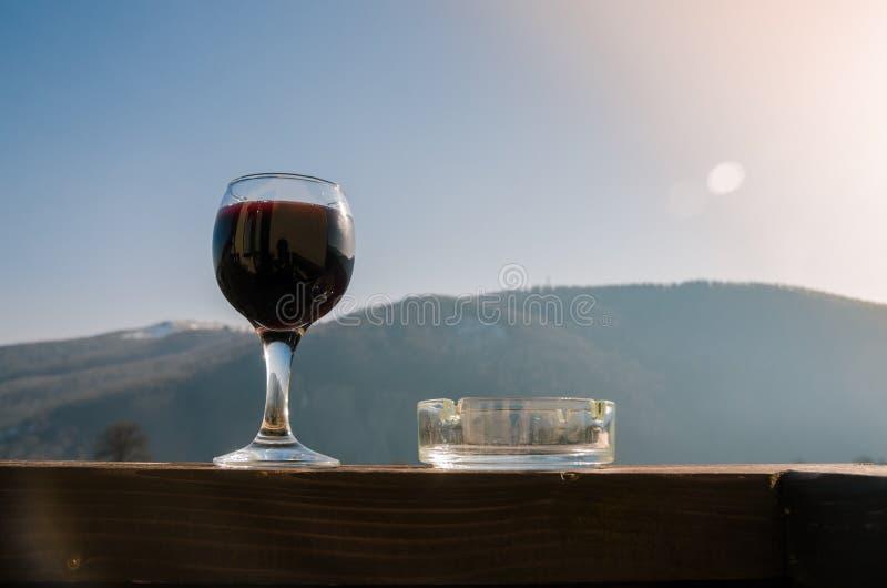 Стекло красного вина и ashtray на предпосылке гор стоковое изображение rf