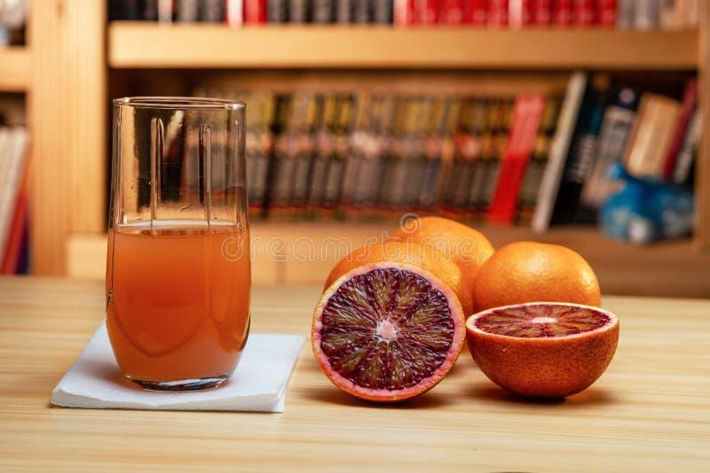 Стекло сока и отрезать красные апельсины на светлом деревянном столе Запачканные книжные полка на заднем плане стоковое фото