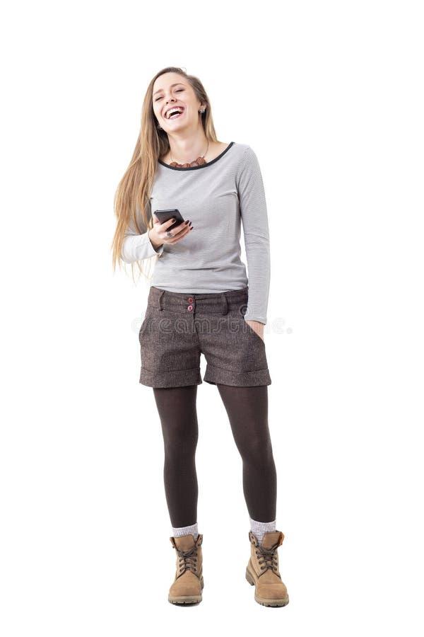 Стильная молодая расслабленная женщина смеясь пока говорящ хэндс-фри на дикторе мобильного телефона стоковое изображение rf