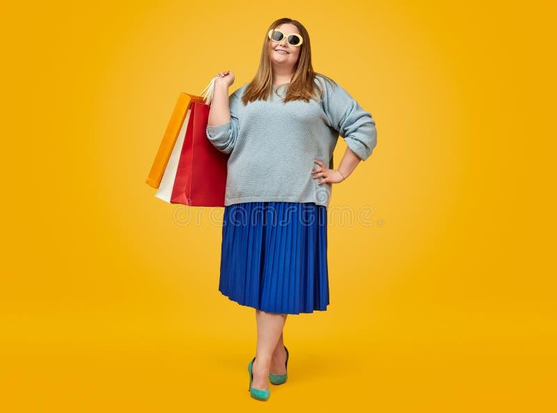Стильная пухлая женщина с бумажными мешками стоковое фото rf