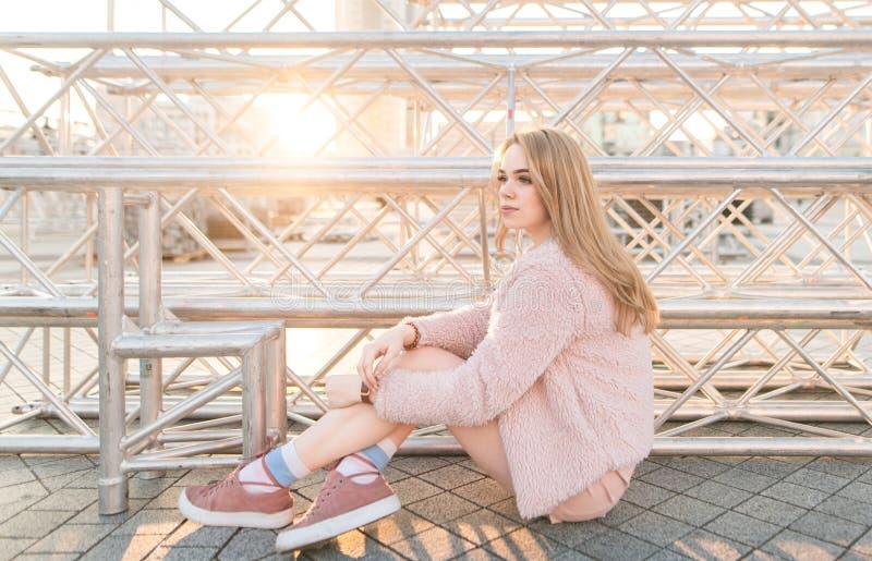 Стильная привлекательная девушка в розовых одеждах сидя на том основании на предпосылке захода солнца и смотря прочь стоковое изображение