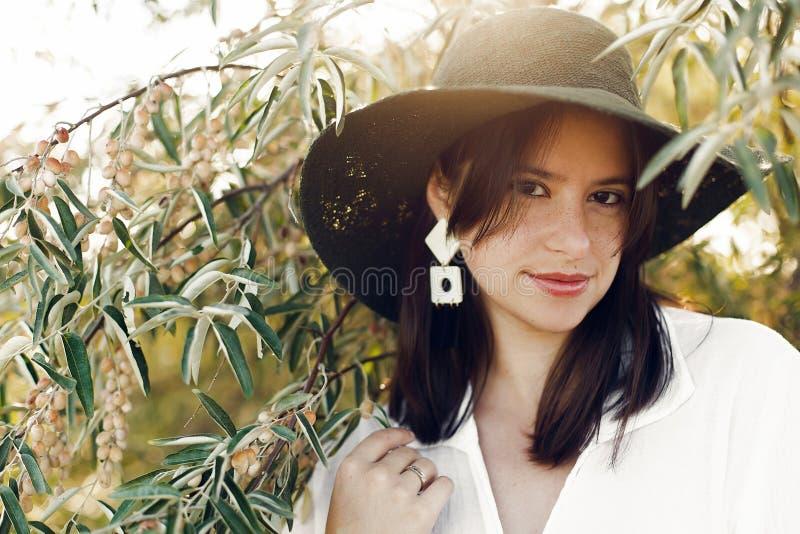 Стильная девушка в шляпе представляя на ветвях оливкового дерева в теплом солнечном свете Счастливая молодая женщина boho с естес стоковые изображения