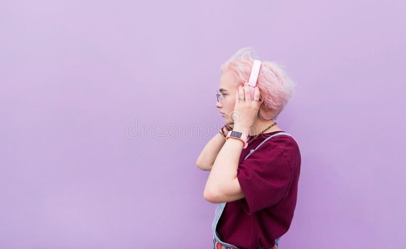 Стильная девушка слушает музыку в розовых наушниках на пурпурной предпосылке стоковое изображение
