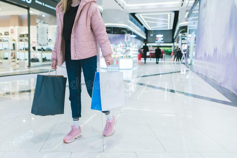Стильная девушка с покупками в ее руках идет через современный, красивый торговый центр Девушка ходит по магазинам стоковое фото rf