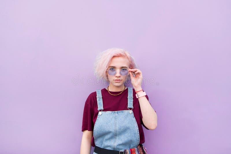 Стильная девушка с розовыми волосами и солнечными очками пурпурная предпосылка и взгляды на камере стоковые фото