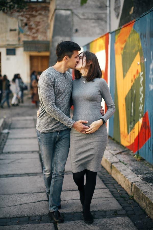 Стильные беременные пары держа руки на рему младенца и идя в улицу города Счастливые молодые родители, мама и папа, обнимая живот стоковая фотография