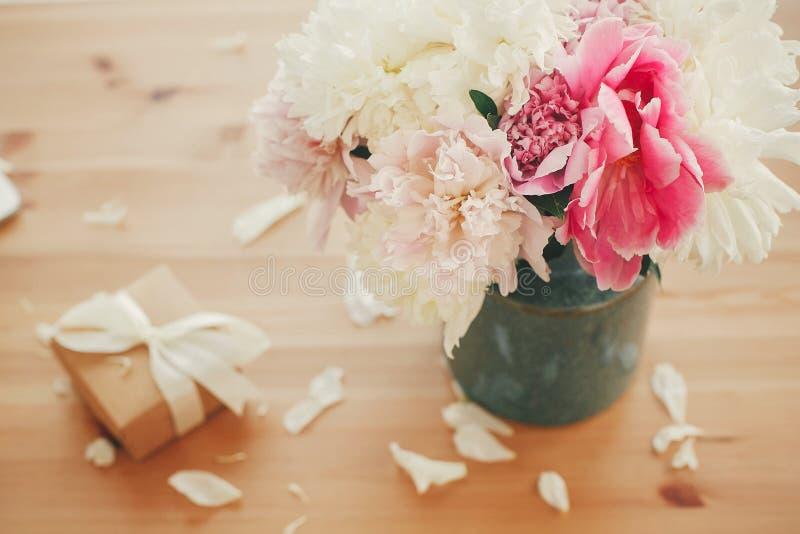 Стильные пионы пинка и белых в вазе и подарочной коробке с лентой на деревянном столе в свете, космосе для текста мать s дня счас стоковое фото