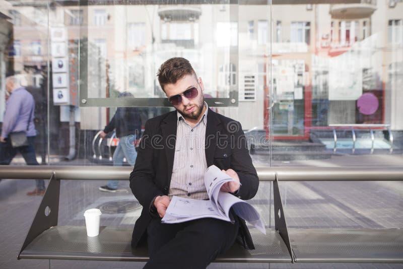 Стильный бизнесмен в его стеклах и документах в его руках сидит на стенде стоковое фото rf