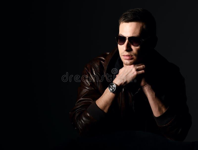 Стильный успешный богатый человек в черной футболке и коричневой кожаной куртке сидит и думает что-то сверх стоковые фотографии rf