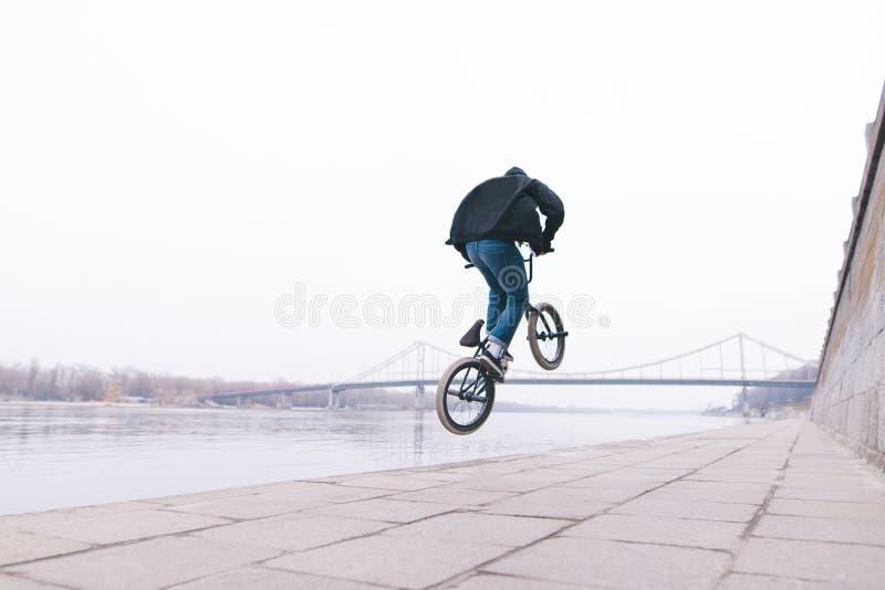 Стильный человек делает эффектные выступления на велосипеде BMX в outdoors Фристайл на BMX На портовом районе стоковая фотография rf
