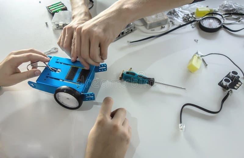 Студенты делая будущий робот Робототехнический, учащ, технология, образование для детей стоковая фотография