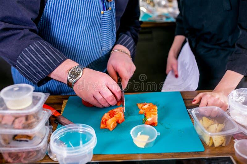 Студент показа шеф-повара как отрезать томат Мастерский класс в кухне Процесс варить Шаг за шагом консультационо Конец-вверх стоковое фото rf