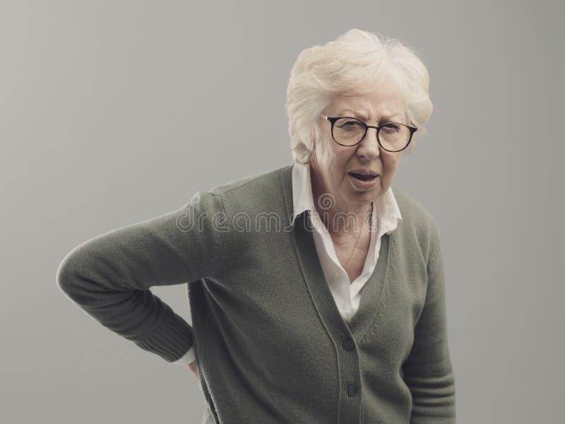 Страдая старшая дама с болью в спине стоковая фотография
