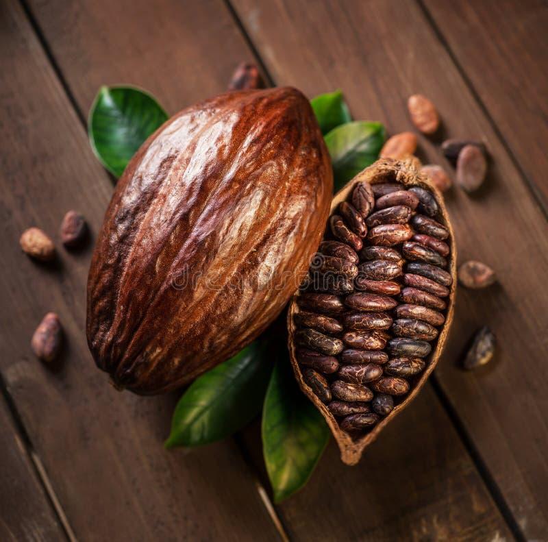 Стручки и бобы кака какао на деревянном столе стоковое изображение rf