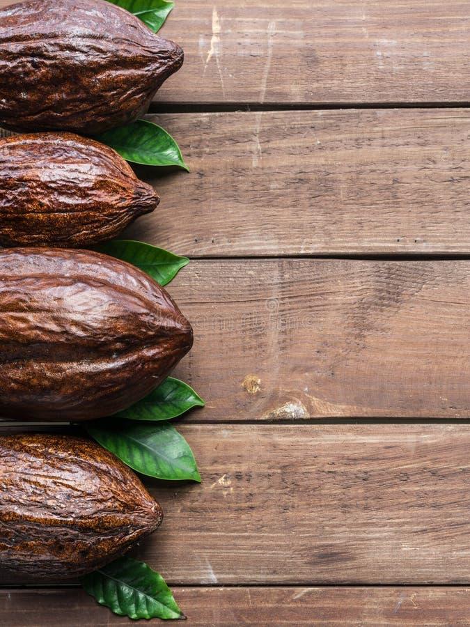 Стручок какао и листья какао аранжированные как часть рамки на деревянной предпосылке стоковое изображение