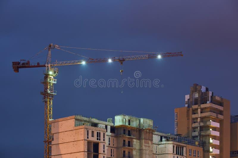 Строительная площадка с кранами на темной предпосылке неба вечером стоковые фотографии rf