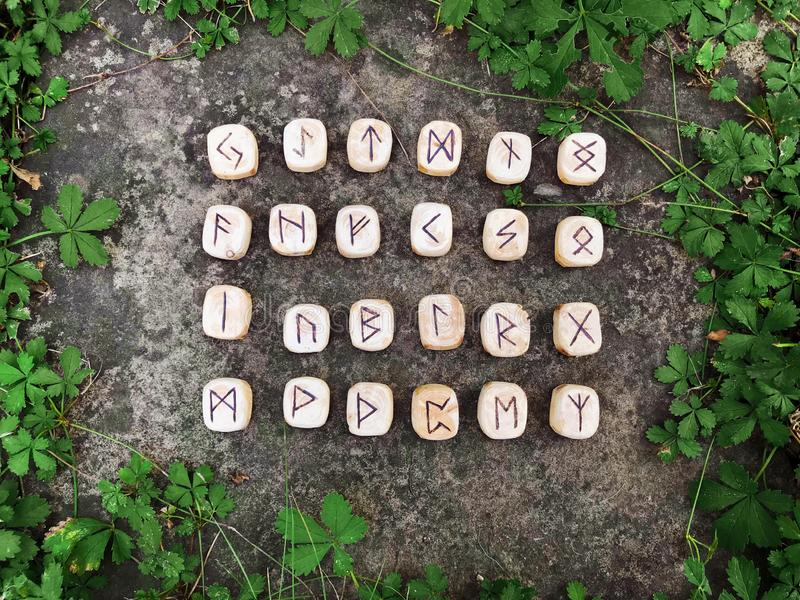 Стог деревянных runes на runes леса деревянных лежит на предпосылке утеса в зеленой траве Runes отрезаны от деревянного стоковое фото