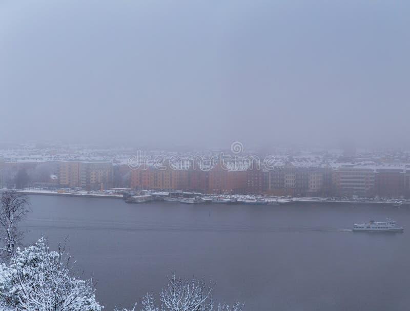 Стокгольм Швеция, туманный взгляд утра над рекой с движением шлюпки и старыми зданиями стоковые фото