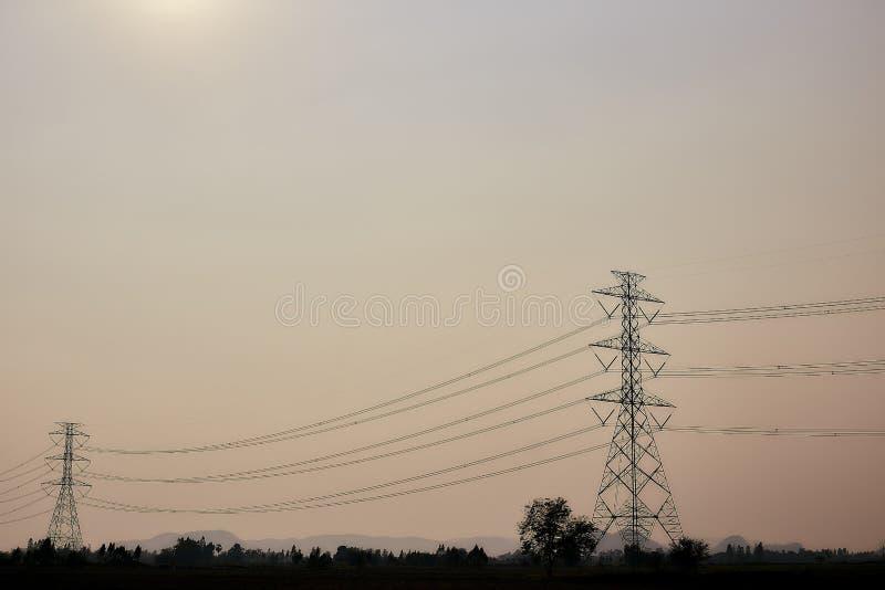 Столб электричества силуэта против захода солнца стоковое фото rf