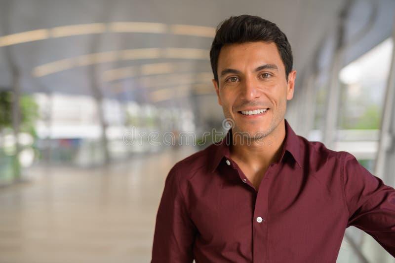 Сторона счастливого испанского бизнесмена усмехаясь на footbridge стоковое изображение