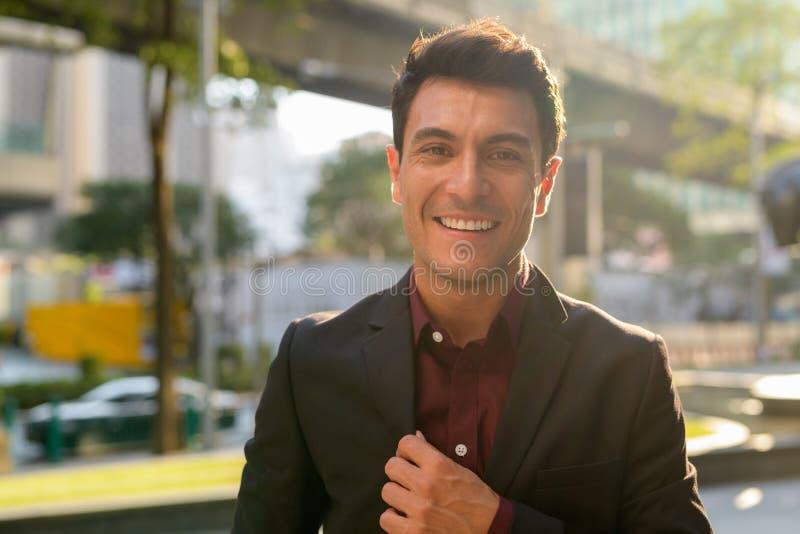 Сторона счастливого молодого испанского бизнесмена усмехаясь в городе outdoors стоковые изображения