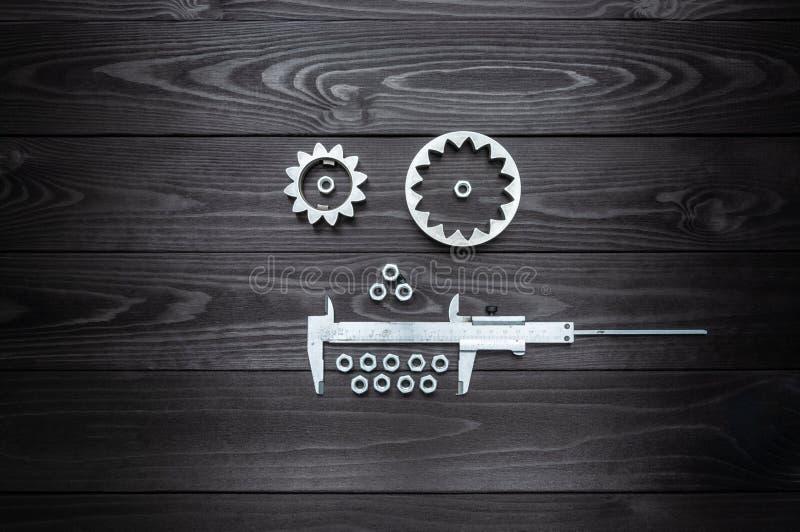 Сторона робота от шестерней инструмента и гаек на деревянной предпосылке стоковое изображение rf