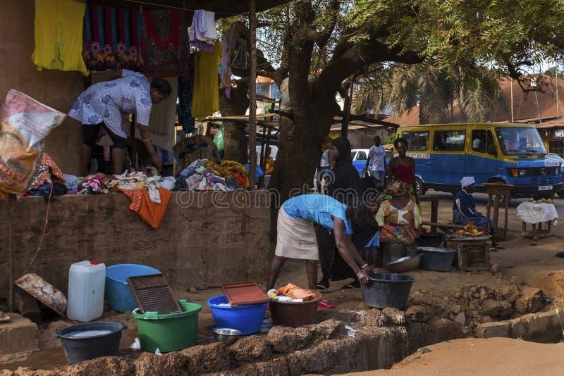 Сцена улицы в городе Бисау с женщинами моя одежды перед их домом стоковые фото