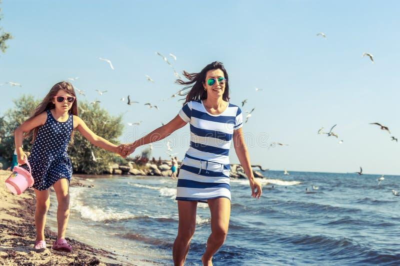 Счастливая беспечальная семья бежать на пляже на море стоковое изображение rf